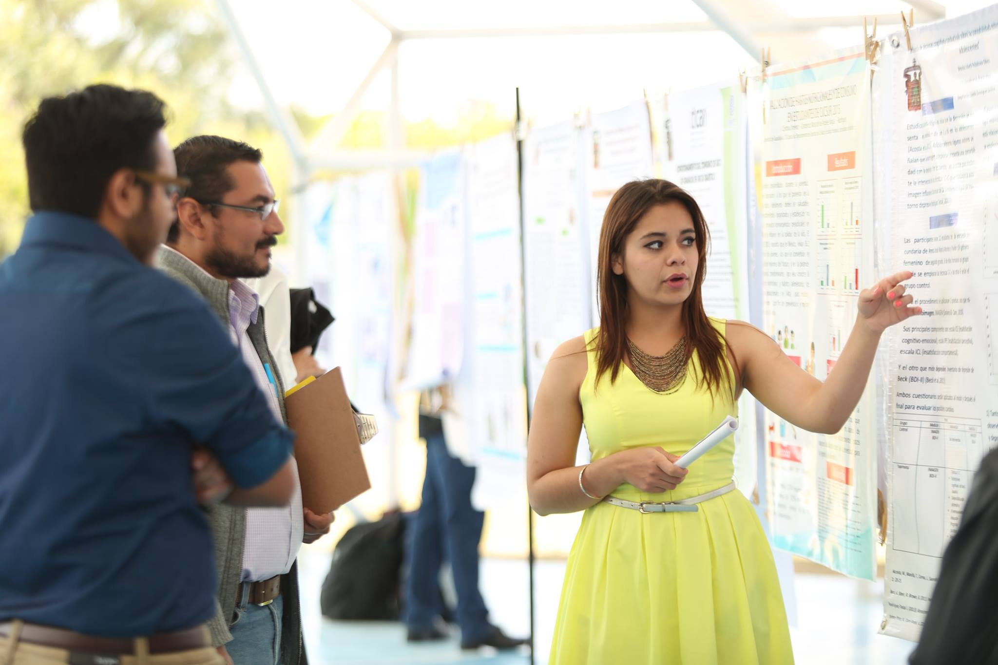 Alumna expone sus cartel ante evaluadores del EICS